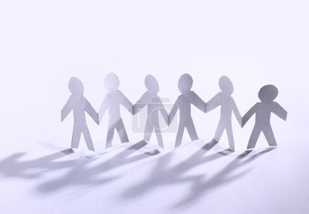 Team of paper doll holding hands