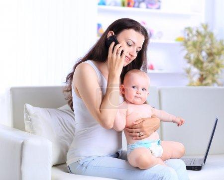 Photo pour Mère et bébé dans siège social avec ordinateur portable et téléphone - image libre de droit