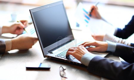 Close up of business team with files and laptop computer in office