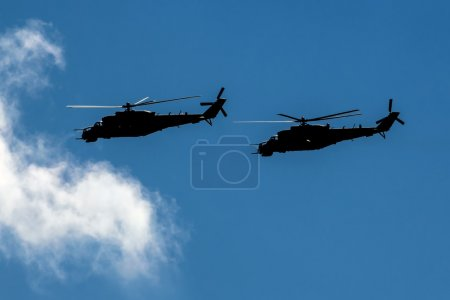 Two combat helicopters silhouettes flying in formation