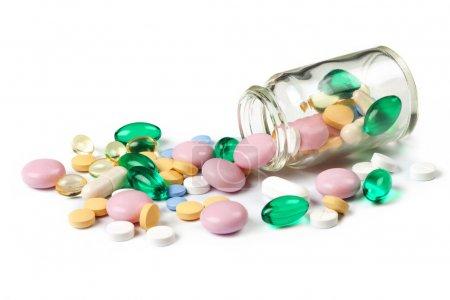 Photo pour Des pilules multicolores se déversent du petit pot, bouteille, isolé sur blanc - image libre de droit