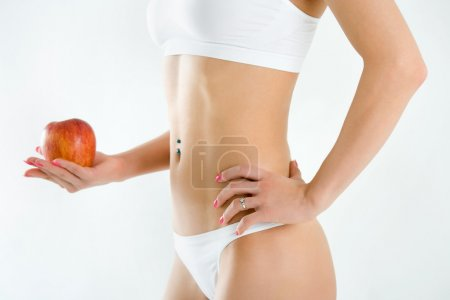 Young woman body and hand holding red apple isolated on white