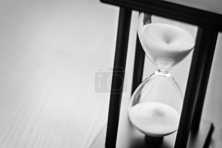 Photo for High angle close up view of sand running through an hour glass or egg timer measuring the passing time and counting down to a deadline - Royalty Free Image