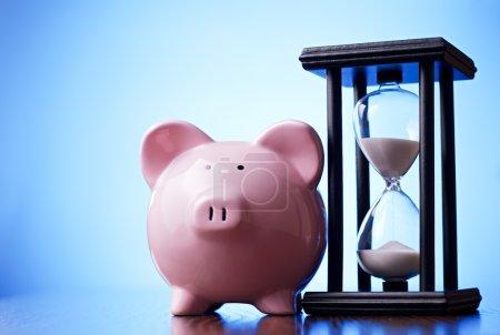 Photo pour Gros plan d'une tirelire en porcelaine rose avec un sablier vintage derrière, concept d'économie d'argent et de passage du temps - image libre de droit