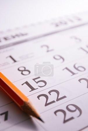 Photo pour Gros plan d'un crayon aiguisé sur la page d'un calendrier, afin de marquer les jours avec des événements - image libre de droit