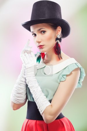 Photo for Young beautiful woman with red glamour lips and eye arrow make-up wearing fancy plastic earrings, top hat and white formal gloves, on coloured background, retro beau - Royalty Free Image