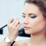 Make-up artist applying bright base color eyeshado...