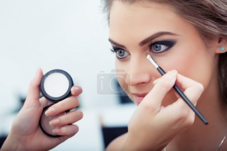 Photo for Make-up artist applying white eyeshadow in the corner of model's eye and holding a shell with eyeshadow on background, close up - Royalty Free Image