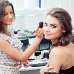 Make-up artist applying powder with a brush on mod...