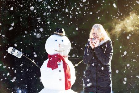 Photo pour Jolie fille blonde dînant du thé en plein air avec bonhomme de neige pendant qu'il neige - image libre de droit