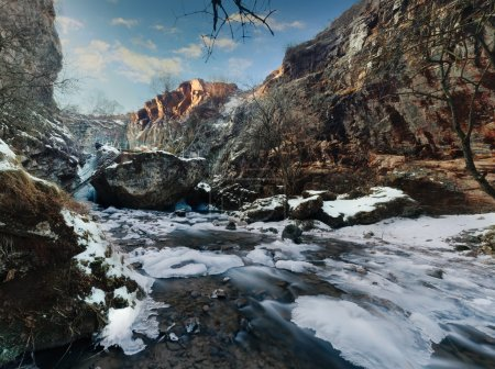 Photo for Winter stream encased in ice with a fresh dusting of snow. Long exposure, with blurred water. Honey waterfalls near Kislovodsk, Russia. - Royalty Free Image