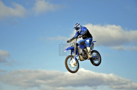 Flight of biker motocross against the blue sky and clouds