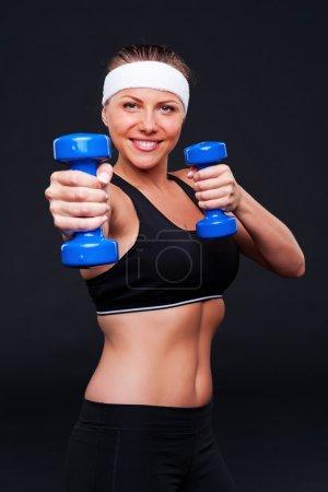 Photo pour Jeune femme faisant des exercices avec haltères et souriant. studio tourné sur fond noir - image libre de droit