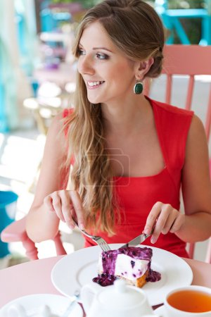 woman eating tasty cake and smiling