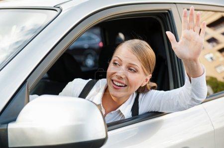 Frau sitzt im Auto und winkt mit der Hand