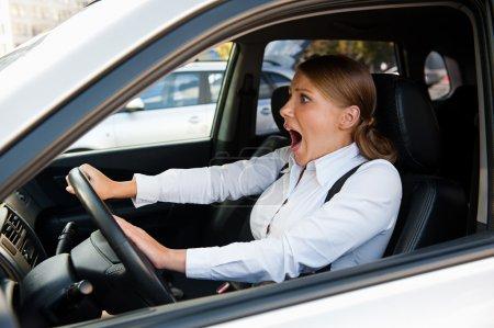 Frau fährt Auto und hupt