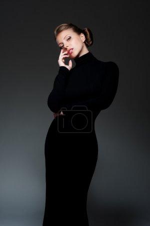 Photo pour Femme glamour en robe noire longue posant sur fond sombre - image libre de droit