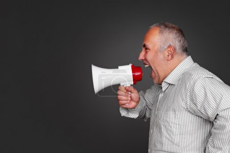 Photo for Sideview of senior man with megaphone over grey background - Royalty Free Image