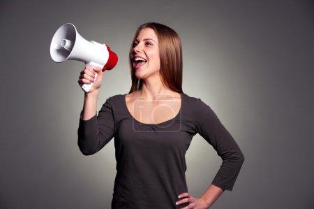 Photo pour Femme heureuse avec haut-parleur sur fond sombre - image libre de droit