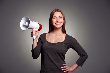 Photo pour Sympathique jeune femme tenant mégaphone et souriant. studio tourné sur fond sombre - image libre de droit