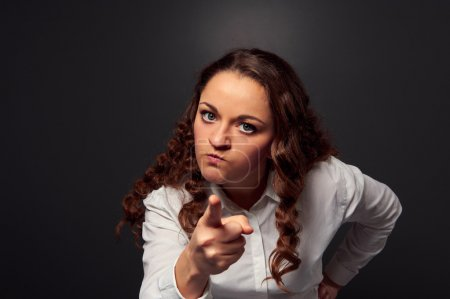 Studio shot of angry woman pointing at camera. pic...