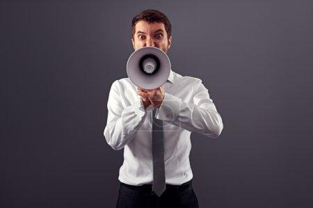 Photo pour Homme en colère émotionnelle criant avec mégaphone sur fond gris - image libre de droit