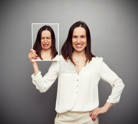 Photo pour Jeune femme heureuse tenant sa triste image - image libre de droit