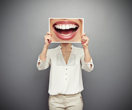 Woman holding picture with big smile. concept phot...