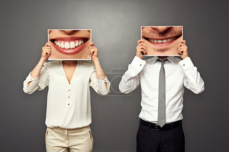 Photo for Woman and man holding pictures with big smile. concept photo over dark background - Royalty Free Image