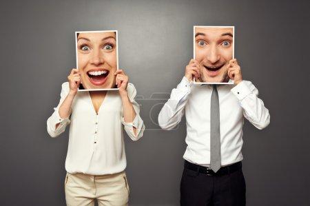 Photo pour Homme et femme tenant des visages heureux étonnés. concept photo sur fond gris - image libre de droit