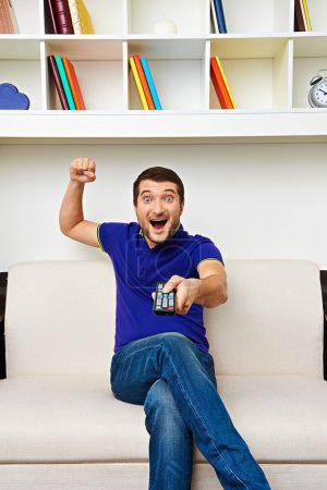 man sitting on sofa and watching tv