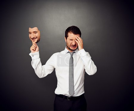 Photo for Crying man holding mask with smiley face - Royalty Free Image