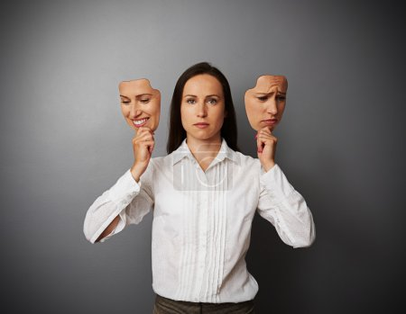 Photo for Young businesswoman woman holding two masks with different mood - Royalty Free Image