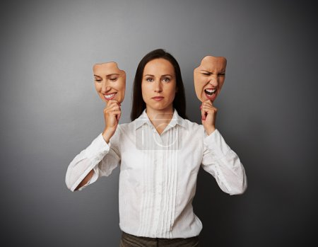 Photo for Serious woman holding two masks with different mood - Royalty Free Image