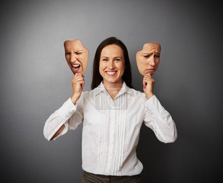 Photo pour Belle jeune femme se cachant sa bonne humeur sous les masques - image libre de droit