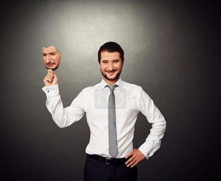 Photo pour Homme d'affaires souriant tenant masque triste sur fond sombre - image libre de droit