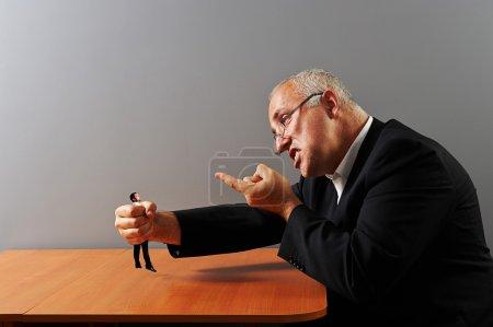 Photo pour Homme d'affaires en colère tenant dans son petit homme de poing - image libre de droit