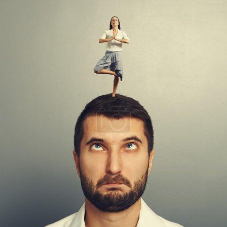 Photo pour Petite femme de méditation debout sur la tête de l'homme insensé - image libre de droit