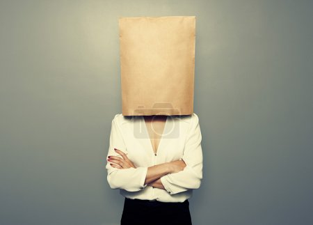 Photo for Businesswoman hiding under empty paper bag over dark background - Royalty Free Image