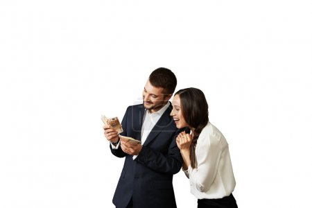 happy laughing couple looking at money