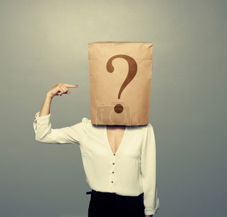 Photo for Businesswoman with paper bag pointing at question over dark background - Royalty Free Image