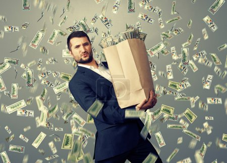Photo for Handsome successful businessman holding heavy paper bag with money under dollar's rain - Royalty Free Image