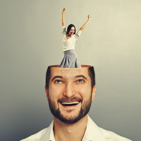 Photo for Laughing young businessman with open head. young excited businesswoman dancing and raising hands up in the man's head. photo over grey background - Royalty Free Image