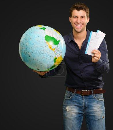 Photo pour Un jeune homme tenant un globe et des billets sur fond noir - image libre de droit