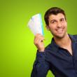 A Young Man Holding Tickets On Green Background...