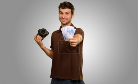 Man Holding Camera And Money