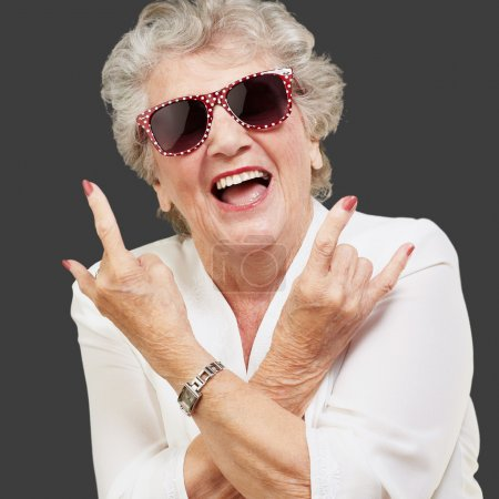 Photo for Senior woman wearing sunglasses doing funky action isolated on black background - Royalty Free Image
