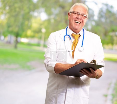 Photo for Happy Male Doctor Writing On Clipboard, Outdoor - Royalty Free Image