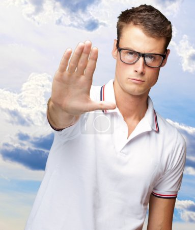 Portrait Of A Handsome Young Man Doing A Stop Symbol