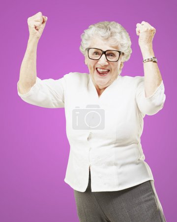 Portrait of a cheerful senior woman gesturing victory over pink